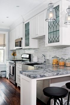 Amazing kitchen features white shaker cabinets paired with quartzite countertops and a linear marble backsplash.