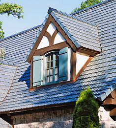 from the site...Tudor cottage style. This arched gabled dormer window is decked out in shutters and extra trim painted to contrast with the stucco.