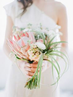 A tropical destination wedding calls for an exceptional, jaw-dropping bouquet! When traditional white roses and lilies just won't do, consider an arrangement featuring flowers and greenery that are locally grown and fillers that enhance the beautiful backdrop nature provides (think lush pinks, oranges, and reds mixed with palm leaves and local fruit). The possibilities are …