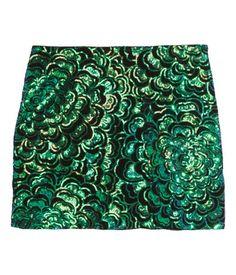 Schwarz/Grün. Kurzer Samtrock mit einem Muster aus aufgestickten Pailletten. Modell mit verdecktem Seitenreißverschluss und Jerseyfutter.