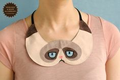 Tard The Grumpy Cat Collar Bib Necklace, €34.90 plus shipping (approximatedly USD $58), by 'PetitiPanda' on Etsy.Com --- Hand wash only. Made with imitation leather, black Swarovski crystals, and velvet ribbon. Made in Germany by Kerstin Bauer. Not an officially licensed product.