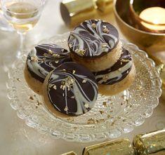 Kage med marcipan udstukket i små runde stykker. Kagen er pyntet med mørk og hvid chokolade