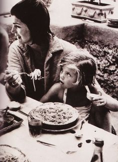 Jackie Kennedy eats spaghetti with Caroline in Italy.