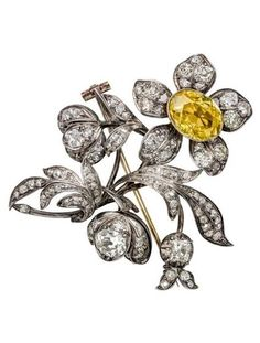 An antique diamond-set floral brooch, 19th century. Set throughout with graduated cushion-shaped diamonds, mounted in silver and gold, the flower head set with an oval-shaped fancy yellow diamond. #antique #brooch