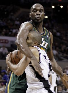 San Antonio Spurs' Tony Parker, front, is fouled by Utah Jazz's Al Jefferson during the third quarter of Game 2 of a first-round NBA basketball playoff series, Wednesday, May 2, 2012, in San Antonio. (AP Photo/Eric Gay)
