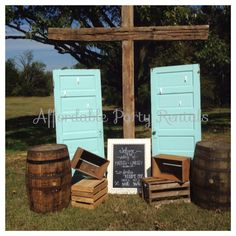 Lovely props for an outdoor wedding! Vintage doors wooden crates whiskey barrels along with a wooden cross made by the Bride and Groom