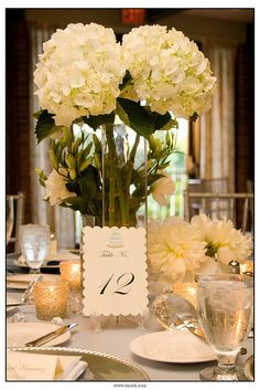 - Tall hydrangea stems in glass vases  - Small white/pink votive candles  - Small single stem flowers in votive holders  Lovely.