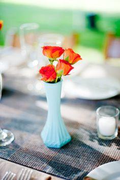 Orange roses in milk glass vase