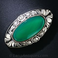 Think green! A 2 5/8 inch by 1 3/8 inch brooch, rendered in silver and adorned all around with foliate repousse, presents a big, bright green oval crysoprase in this charming and striking adornment dating from the turn-of-the-20th century.