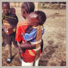 Siblings babywearing in Sudan. Wow...not lookin so comfy though!