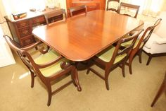 """Expandable double pedestal dining room table, with six matching upholster seat chairs, table is 43.5""""x65.5""""x29.5""""T when closed, having two 15 """" leafs, one armchair with carved scroll decoration, all six chairs with carved ladder backs."""