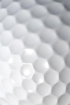 Een golfbal: de structuur is synthetisch materiaal, de textuur is een patroon van zeshoeken en glad.
