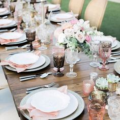 Desert glamourous wedding in Arizona featuring silver accents, patterned white plates, pink goblets, brown goblets, and clear vintage goblets on a wood table.