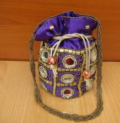 This is a hand embroidered colorful bag made of satin fabric.  It is in pouch (potli) style ideal as a party bag and bridal bag.It is a vintage style bag.  An excellent piece from famous Indian handicrafts from Rajasthan.  It is decorated with metallic antique finish sequins and mirrors.  It has a draw string.It is a wrist let has a handle made of antique finish beads.  Bag is perfect as a gift item. Ideal for functions and parties.  Inside it has enough space to keep your small things…
