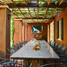 A long dining table sits underneath an arbor covered in vines, creating a wonderfully open atmosphere - Traditional Home® / Photo: John Granen / Landscape architect: William B. Callaway