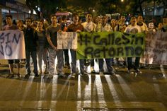 Demonstrators block a street with signs as they shout anti-government slogans to protest the detention of four students in Caracas, Venezuel...