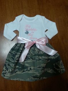 This dress was designed by a special customer. It is embroidered with baby pink thread and has a ribbon that goes completely around the dress and ties in the front. The skirt is made of Airforce fabric. Any little girl wearing this dress will surely make her Daddy proud! It can be bought from newborn to 24 months.long or short sleeves.the design says, My Daddy is my hero, or I can make a different saying if you want. It can also be made in marine or Army fabric.