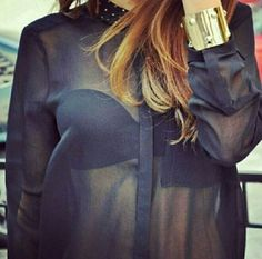 Sheer blouse and gold cuff.