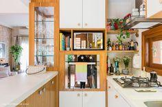 Cozinha tem armários brancos e nichos de madeira.