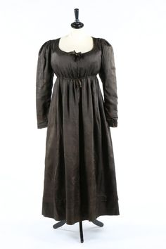 A chocolate brown silk 'Quaker' dress, circa 1818.  A chocolate brown silk 'Quaker' dress, circa 1818. with draw-string to raised waist and neck, with note attached stating it was 'worn by Elizabeth Banks Palmer in 1818', together with a plain linen waist pocket and a padded cotton bum-roll (3). - See more at: http://kerrytaylorauctions.com/one-item/?id=35&auctionid=402#sthash.2UNjdMjp.dpuf