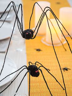 Marching down the dining table, long-legged visitors add arachnid appeal to a Halloween meal. Their twisty limbs can also cling to furniture, banisters, or any other place that could use a little creepy-crawly cool. To make each spider's head and body, use tacky glue to join a small and a large black pom-pom. Glue 2 small jewels to the smaller one for eyes, then set the pom-poms aside to dry. Use wire cutters to cut 4 equal lengths of 18-gauge paper-wrapped floral wire and car...