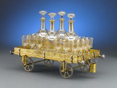A wonderful and rare cavé liqueur, or Gentlemen's Liqueur, in the form of an engraved, doré bronze railway truck. The set is complete with four crystal decanters bearing colorfully enamelled labels (Cassis, Cognac, Anisette, Armanoal) and 16 cordials accented in gold leaf. Two tiny buckets hang from each side for holding matches. Excellent condition. Circa 1880.