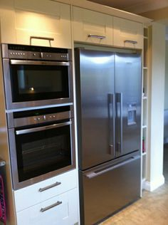 Integrated oven & microwave tower next to American fridge freezer. Separate the two with a 300ml pull out larder.