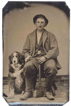 A man, his dog, and his ax, tintype. N.B. I think the man is holding the dog's paw.