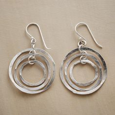 "MOBILE HOOP EARRINGS -- Taking their cue from modernist mobiles, the hand-hammered sterling silver rings in these mobile hoop earrings sway independently, making your every move a work of art. 1-3/8""L."