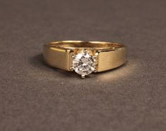 Approximately carat brilliant cut diamond solitaire ring in marked yellow gold. Diamond is approximately clarity, H-I color, set in a wide band mounting. Wedding Rings Solitaire, Diamond Solitaire Rings, Gold Wedding Rings, Tiffany Solitaire, Solitaire Ring Designs, Solitaire Setting, Solitaire Engagement, Mens Gold Rings, Gold Rings Jewelry