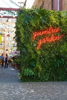 """""""Gumtree Garden Pop-Up Bar,pinned by Ton van der Veer"""" quoted - I friggin love this! The living wall is so lush and wild and then the neon lights burn through with vibrance. Design Exterior, Exterior Signage, Ranch Exterior, Bungalow Exterior, Exterior Stairs, Wall Exterior, Exterior Remodel, Exterior Lighting, Bar Design"""