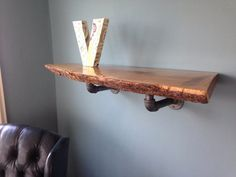 Custom sizing available. White oak live edge slab shelf with industrial iron pipe mounting.