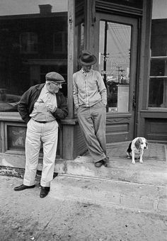 Two men and a dog in front of a small town storefront along the highway  Iowa, 1963  Thomas Hoepker