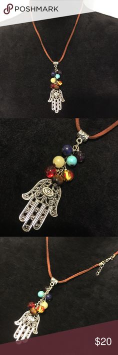 Chakras and Hamsa hand necklace Handmade by me  by far my favorite piece I've made. Fatima hand with chakras, love it!  Brown leather cord. I can adjust cord to desired length.  The seven chakras are the centers in our bodies in which energy flows through.   The Hamsa Hand is an ancient Middle Eastern amulet symbolizing the Hand of God. In all faiths it is a protective sign. It is also identified as the Hand of Miriam, Aaron and Moses's sister, and the Hand of Fatima. Jewelry Necklaces
