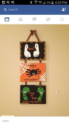 Halloween Family Craft with hands, feet, paint, canvases, & ribbon.