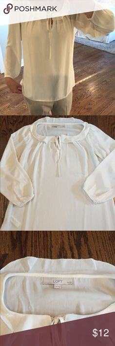 Ivory LOFT scoop neck ruffle top This cream colored scoop neck top from Ann Taylor Loft has a soft, feminine feel.  The crop buttoned sleeves and tie front add style. Gorgeous for work, but don't underestimate the potential with a pair of destructed jeans! Size Small P.  Gently worn - see last pic for tiny little spot. LOFT Tops Blouses