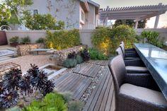 Fantastic design. Architectural plants, water feature, zinc bar, love the gabions.