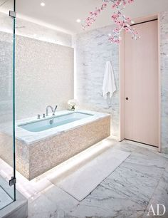 The wife's bath is accented with a chandelier by Studio Tord Boontje for Swarovski and custom-made mother-of-pearl mosaic tiles; the tub is by Duravit, with fittings by Fantini.