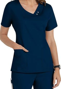 An asymmetrical V-neck top features multiple pin-tucks, tonal snaps and zig zag stitching. Release darts at back waist, front curved patch pockets, and side vents complete the picture. Center back measures Poly Rayon Spandex Twill Scrubs Outfit, Scrubs Uniform, Scrubs Pattern, Stylish Scrubs, Cute Scrubs, Womens Scrubs, Uniform Design, Nursing Dress, Asymmetrical Tops