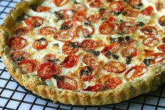 Tomato MozzarellaTart. Basil is in the crust. My mouth is yearning for this tempting tart now. YUM.