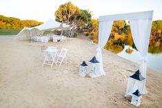Wedding ceremony - White wooden arbour with chiffon curtains and nautical lanterns