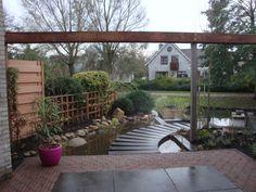 Vanaf het terras aan het huis over de vijver naar het terras aan het water.