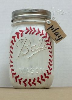 """Baseball Painted Mason Jar. Used Folk Art Chalk paint, added details with small brush and F/A enamel paint, dried, sanded, sealed with spray acrylic sealer. For detail work, used pencil to add a circle as a guide for stitching, 1 on each side of jar. Covered lid with burlap inside rim. Used wire to attach a small tag that says """"play"""". Tag has eyelet, word added with stickers. by jaclyn"""