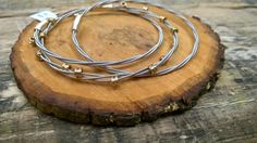 Three bracelets made from recycled guitar strings!  Electric guitar strings, brass ball end beads and gold jewelry wire.  Handmade in New Jersey.