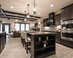 living room kitchen open concept with light wood floor dark cabinetry - Google Search