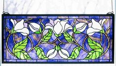 Features:  -Mounting bracket and jack chain included.  -Tiffany original design captures the beauty of the magnolia in full flower.  -Stained art glass and encased in a solid brass frame, each window