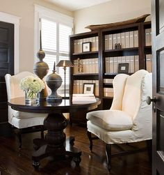 a small bedroom into a home office. A Drexel Heritage round table doubles as a desk where I can look over design options with clients. Shelves hold client files in linen binders.