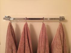 Shower hooks on towel rack for extra storage space.