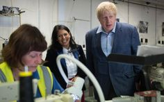 Priti Patel and Boris Johnson inspect sewing machines during a visit of…
