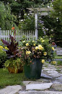 """A pergola, white picket fence, winding stone path and """"cottagey"""" container gardens. From a post on cottage garden style on Tesselaar Plants' Your Easy Garden blog. www.youreasygarden.com"""